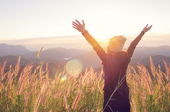 Carefree Happy Woman Enjoying Nature on grass meadow on top of m